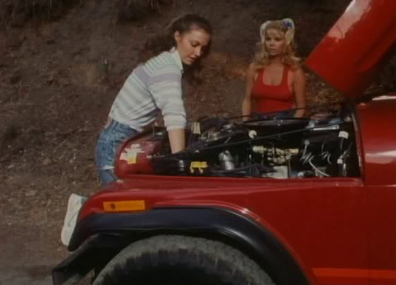 That's here on the right, taking charge as an attractive young woman tries to get an old banger fired up
